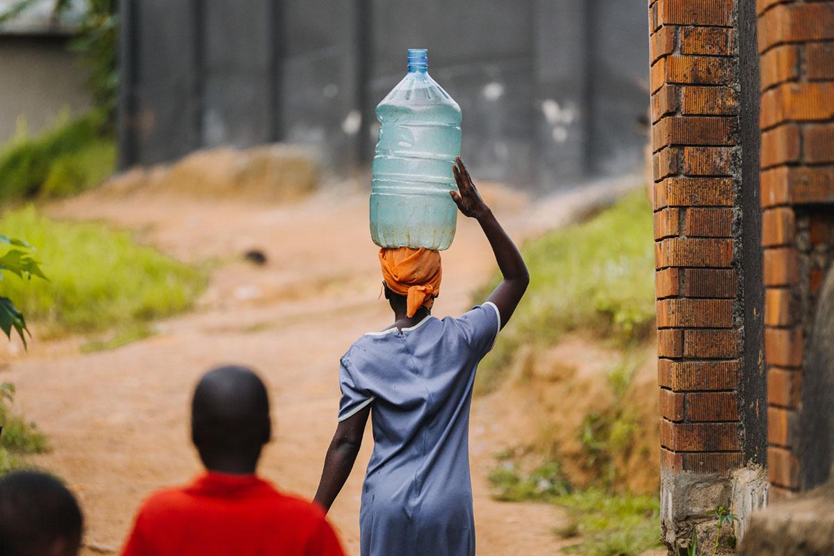Afrikansk kkvinne fra Uganda bærer vann på hodet
