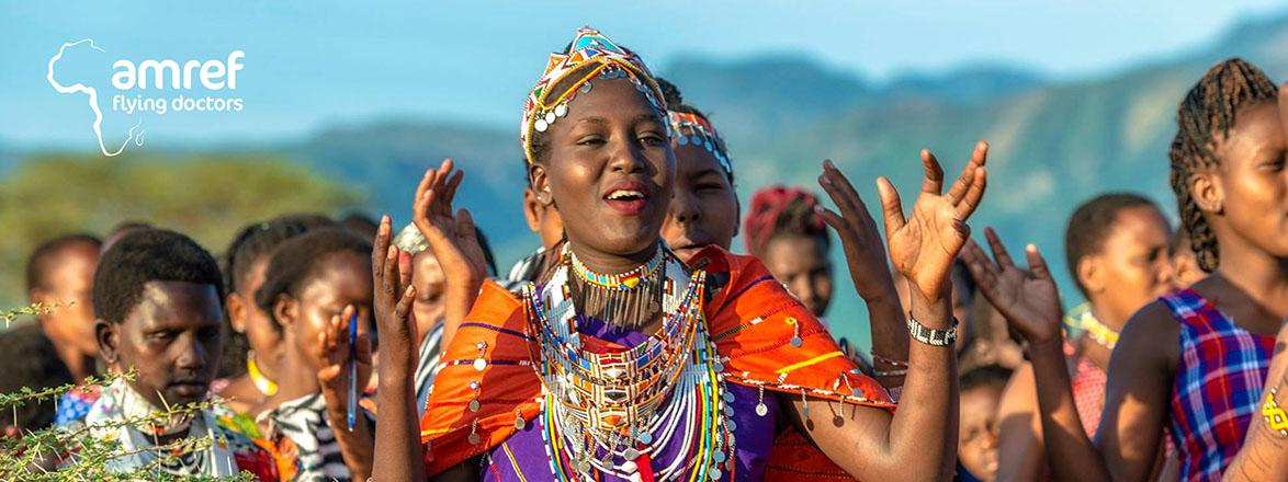 Klappende, glade jenter i fargerike, tradisjonelle klær