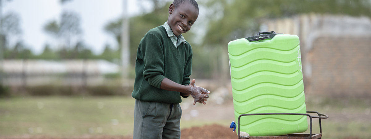 Smiling young boy African washing hands