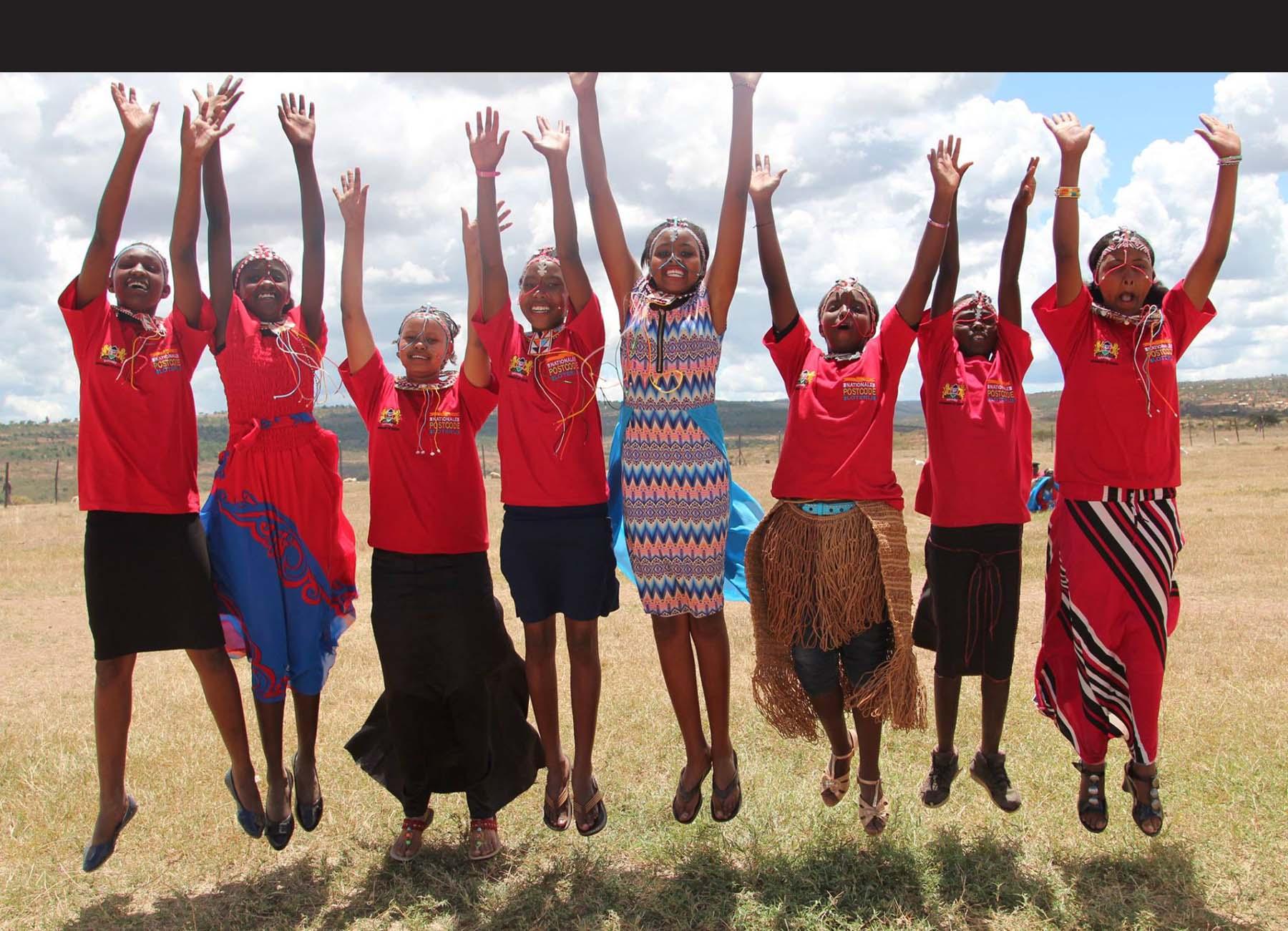 Hoppende glade barn i røde drakter strekker hendene mot himmelen svart strek øverst